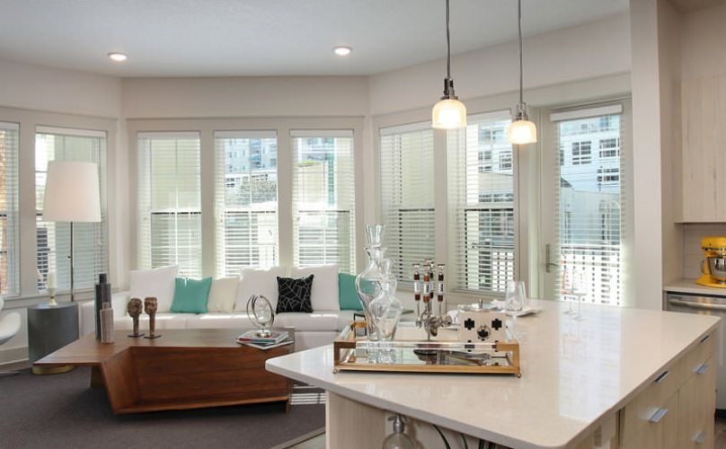 open concept apartment layout with pendant lights over kitchen island
